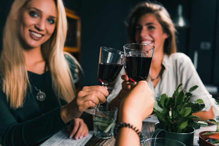 Cheerful Female Friends Toasting Wineglass At Table In Restaurant