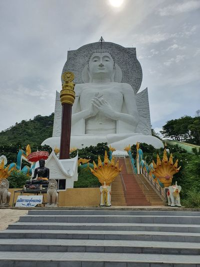 Statue outside temple against building and sky