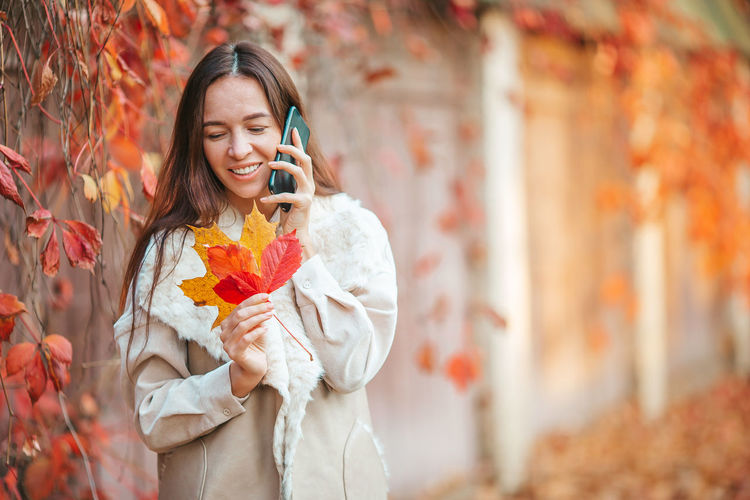 Full length of a smiling young woman holding autumn leaf