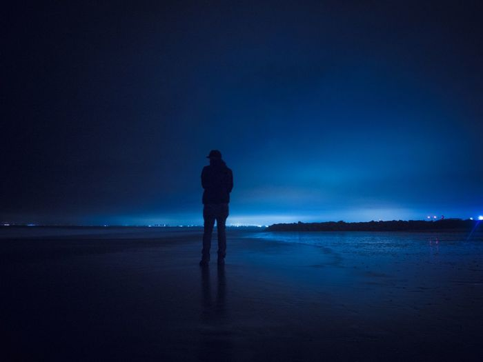 Woman standing at sea against sky at night