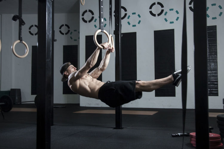 Full length of shirtless man exercising at gym
