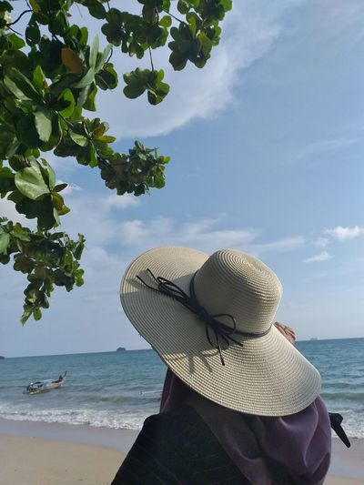 Rear view of woman wearing hat looking at sea against sky