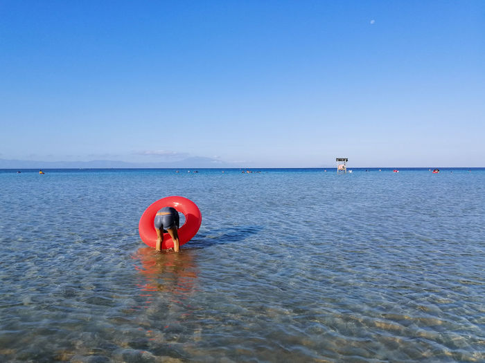 Red floating on sea against clear blue sky