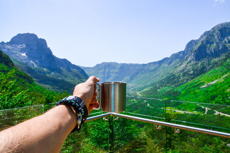 Man Holding Mug By Mountain Against Clear Sky