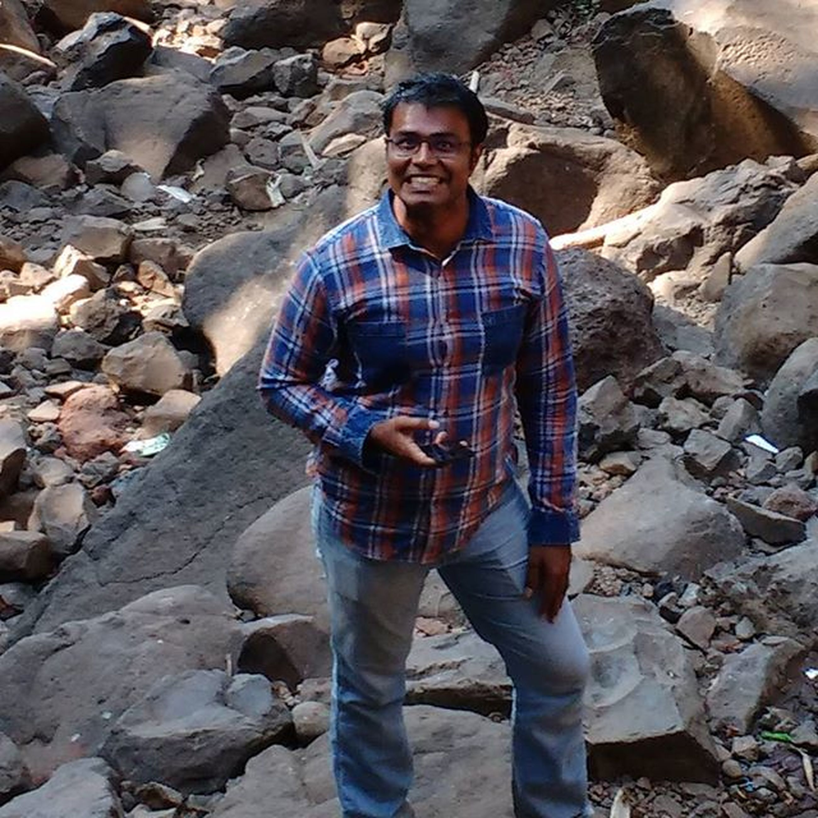 lifestyles, casual clothing, standing, leisure activity, rock - object, person, portrait, looking at camera, full length, front view, young adult, outdoors, day, stone - object, three quarter length, nature, high angle view, rock