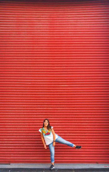 Full length portrait of woman standing against red shutter