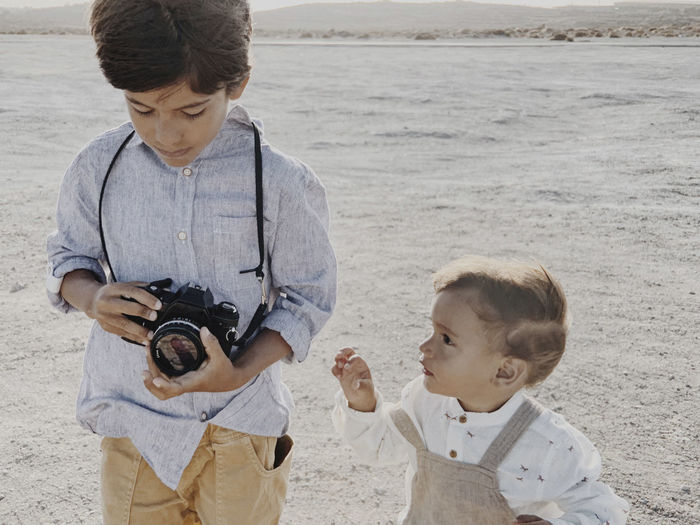 Boy photographing with woman standing on beach
