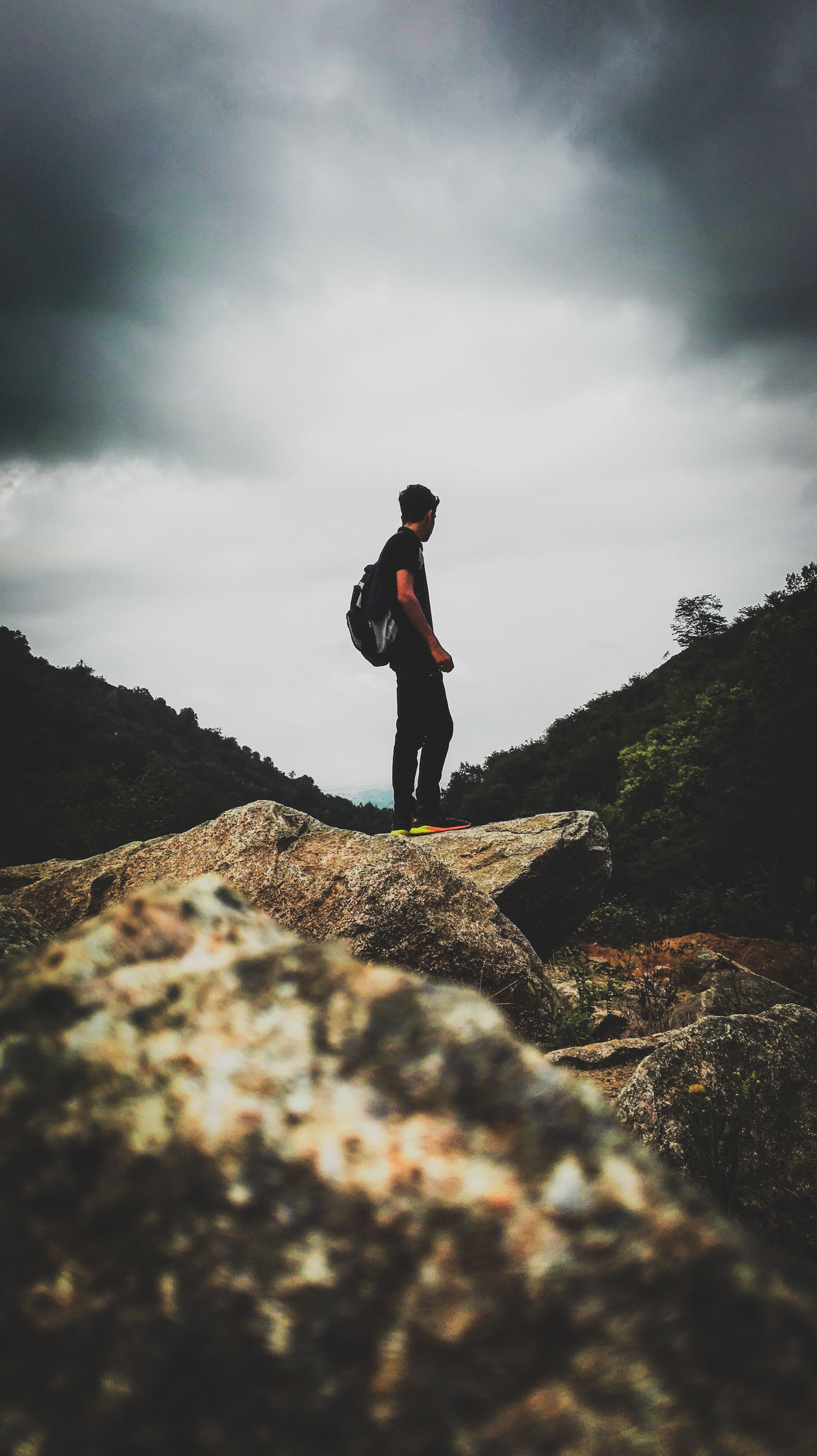 cloud - sky, sky, one person, rock, solid, leisure activity, real people, standing, lifestyles, rock - object, day, nature, full length, mountain, beauty in nature, men, scenics - nature, side view, outdoors
