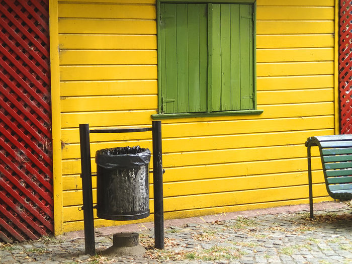 black garbage can in front of a multicolored house facade with door, bench and window Carbage Containers Carbage Cans Garbage Rasta Colors RASTA Bench Buenos Aires, Argentina  La Boca, Buenos Aires Building Exterior Closed Window  Garbage Can Green Yellow Red  Multi Colored Multicolored House Facade Multicolored Houses No People Outdoors Window Yellow