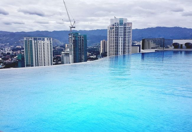 Infinity and beyond... Architecture Skyscraper Building Exterior Built Structure City Cloud - Sky Modern Outdoors Cityscape Water No People Urban Skyline Sky Travel Destinations Sea Day Swimming Pool Infinity Pool Philippines Investing In Quality Of Life EyeEmNewHere