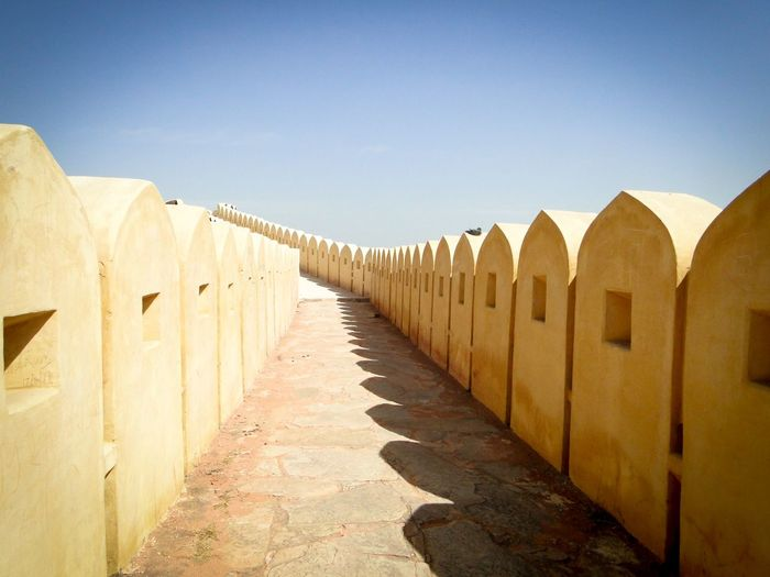 Walkway Amidst Retaining Walls Against Sky