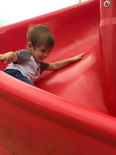 Boy enjoying on slide at playground