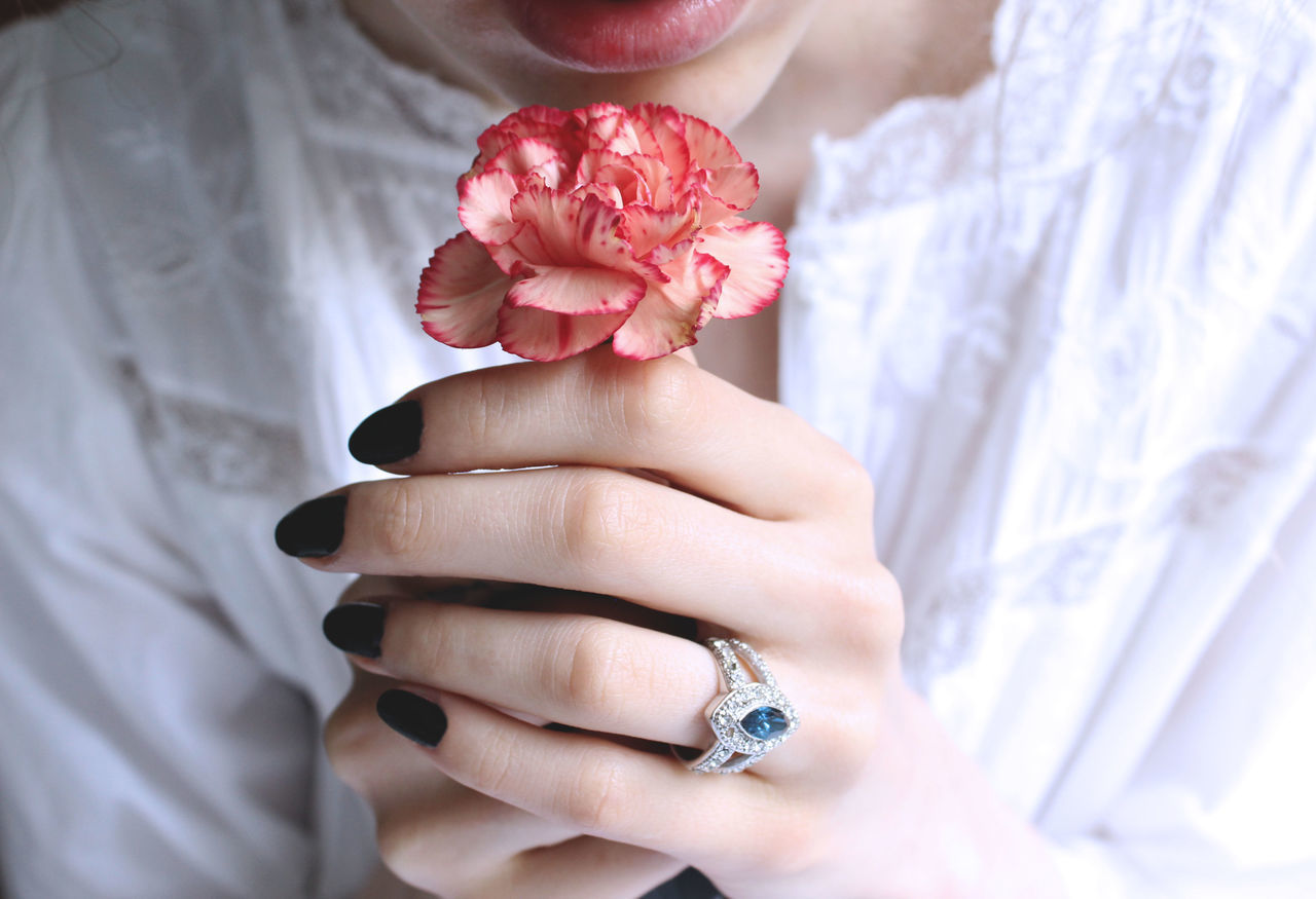 Midsection of woman holding carnation flower