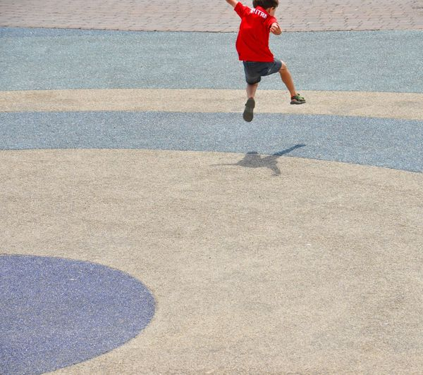 Rear View Of Boy Jumping At Playground During Sunny Day
