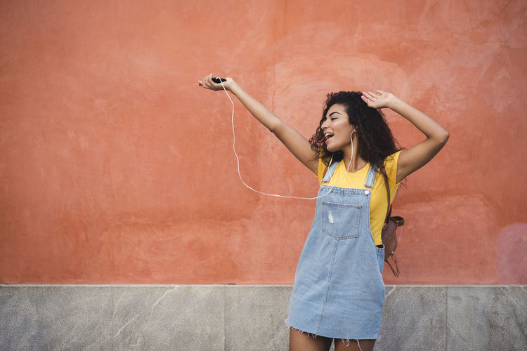 beautiful mixed girl listening to the music happy in the street Arms Raised Beautiful Woman Body Part Emotion Front View Hair Hairstyle Happiness Holding Human Arm Human Limb Lifestyles Limb One Person Smiling Standing Three Quarter Length Wall - Building Feature Women Young Adult Young Women