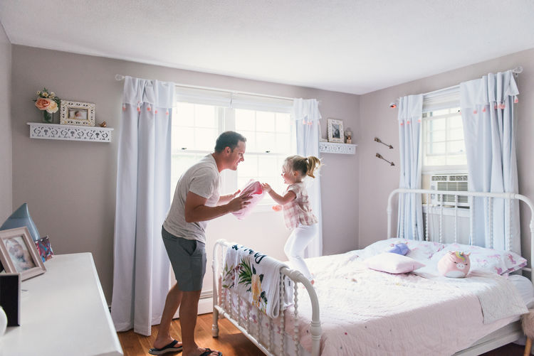 Side view of couple standing on bed