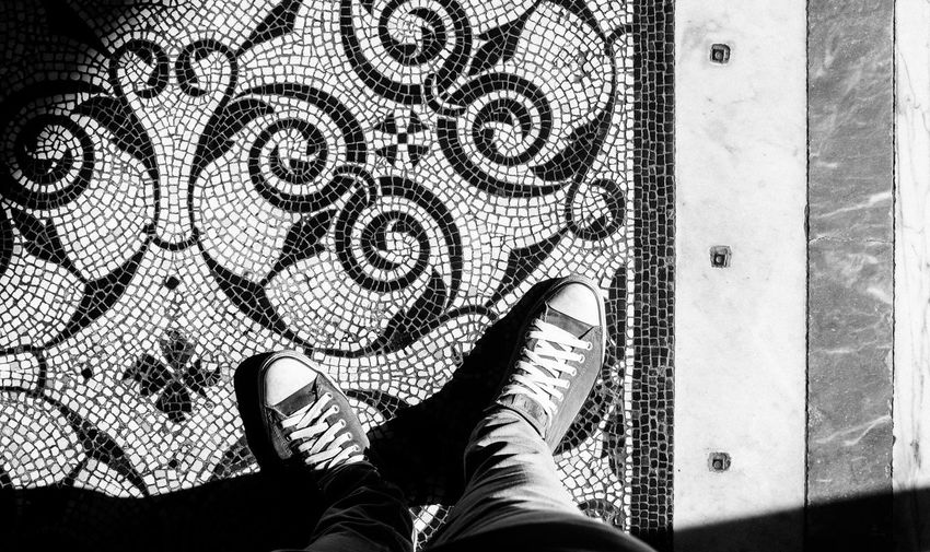 Low section of man standing on tiled floor pattern