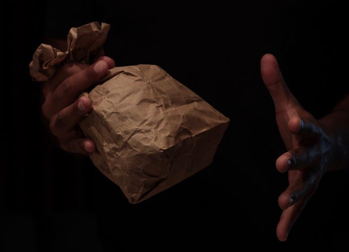 Close-Up Of Human Hand Holding Paper Bag Against Black Background