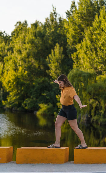 Full length of woman walking against tree