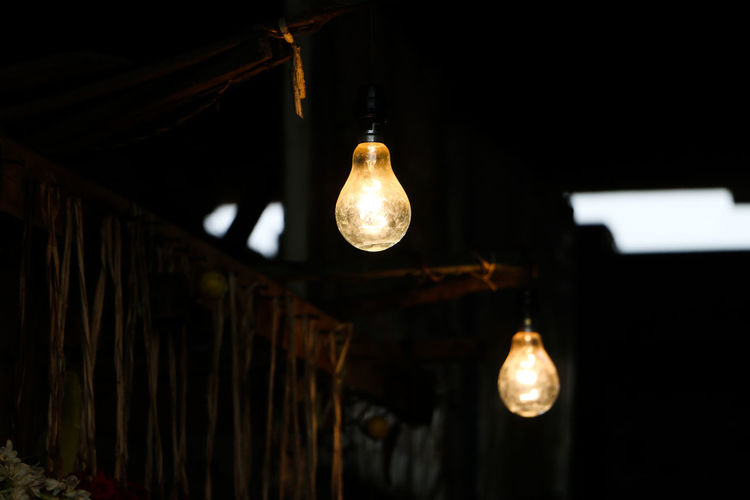 Low angle view of illuminated light bulbs hanging in dark