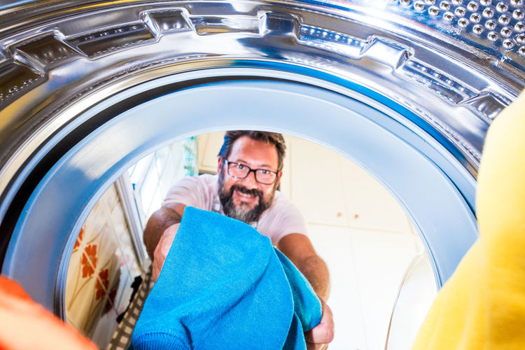 Portrait of man putting clothes in washing machine