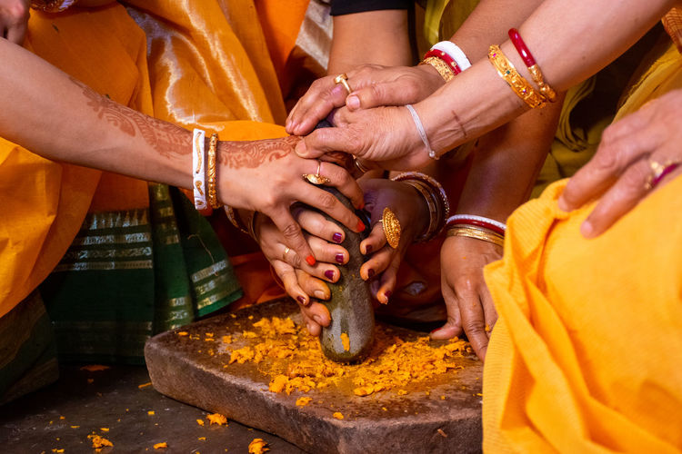 Midsection of women grounding turmeric on stone