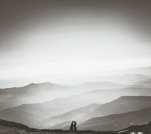 Silhouette Of Couple Kissing On Mountain Against Clear Sky