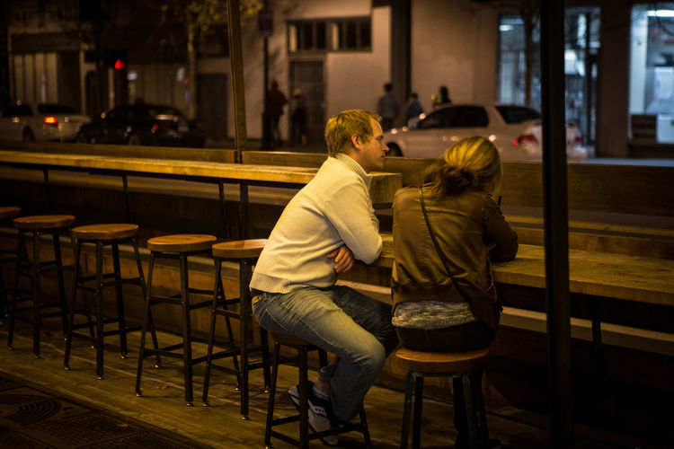 Architecture Casual Clothing Chair City Life Conversation Couple Days Ago Lifestyles Night Out Night Photography Outdoor Seating Parklet Real People Restaurant Sitting Street Street Photography Table Togetherness Cities At Night