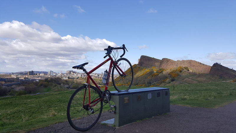 Bicycle Cycling Transportation No People Cloud - Sky Day Sky Outdoors Grass Mountain Bike Edinburgh Arthurs Seat Travel Destinations Vacations Togetherness Lifestyles Grass Beauty In Nature Working Field Nature