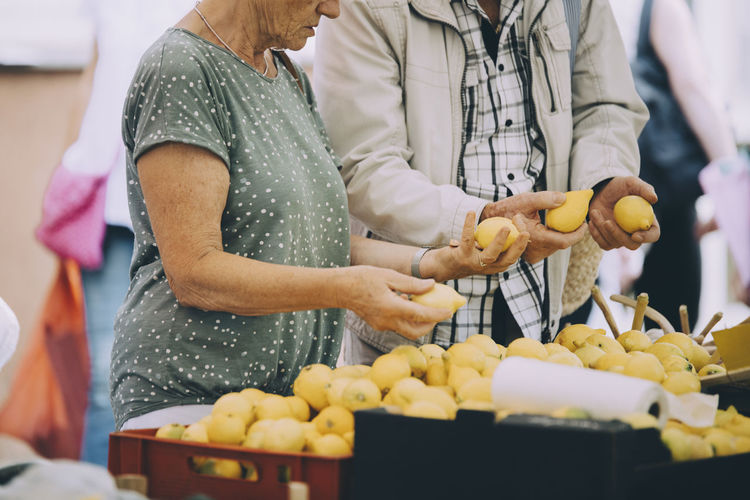 Midsection of man and woman standing at market stall