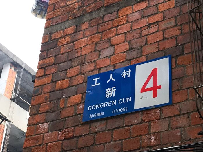 Low angle view of road sign against brick wall