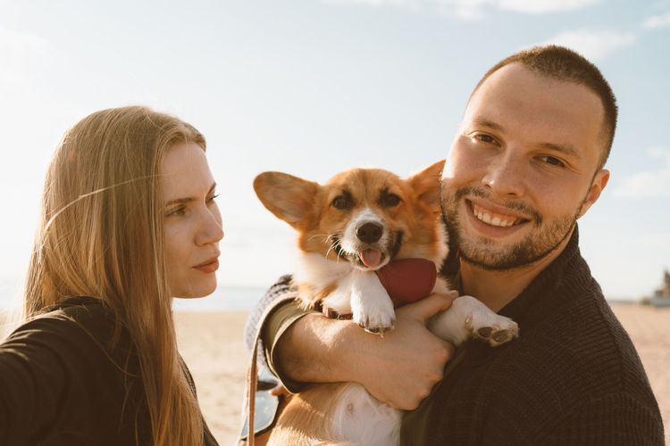 Smiling couple with dog at beach