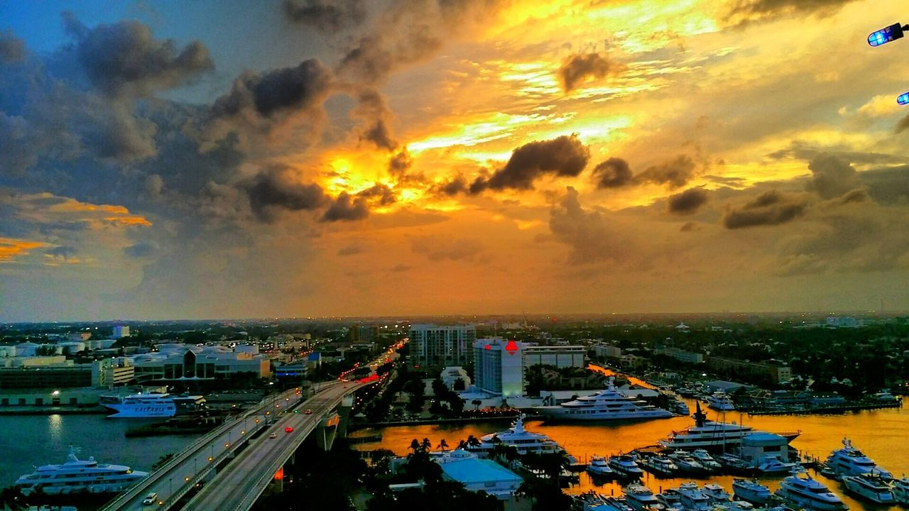 sunset, architecture, transportation, building exterior, built structure, sky, cloud - sky, city, sea, water, cityscape, high angle view, horizon over water, mode of transport, outdoors, city life, nautical vessel, car, road, no people, nature, skyscraper, harbor, day