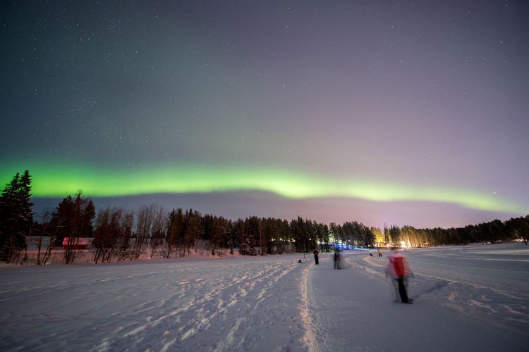 Blurred motion of people on snow covered field against aurora borealis at night