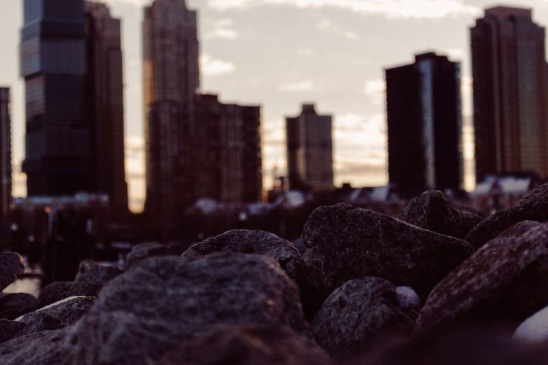 Rocks against buildings in city at sunset