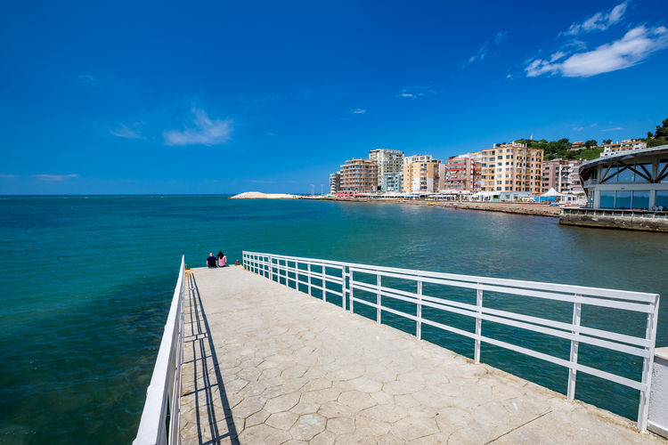 Unrecognizable couple is sitting on concrete boardwalk and enjoying modern cityscape in Albania, city of Durres by Adriatic Sea. Beautiful springtime day with clear blue sky. Albania Albanian Albanian View Water Architecture Built Structure Sky Sea Building Exterior Nature Railing Blue City Beauty In Nature Cloud - Sky Day Transportation Nautical Vessel Scenics - Nature Horizon Over Water Outdoors Travel Destinations No People Promenade