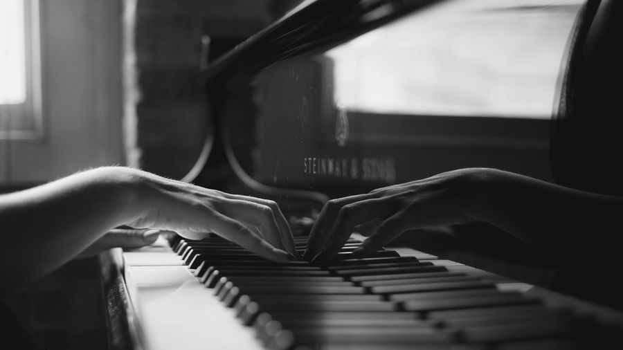 Midsection of person playing piano