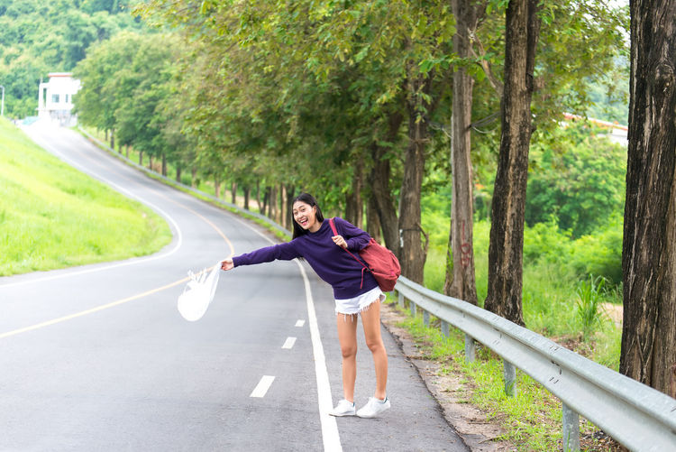 Woman on road amidst trees