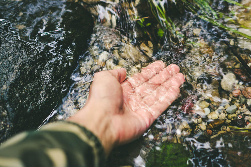 High angle view of human hand on rock and flowing water