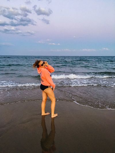 Side view of playful woman standing on shore against sky