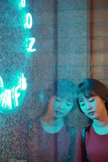Young woman reflecting on wall with illuminated text