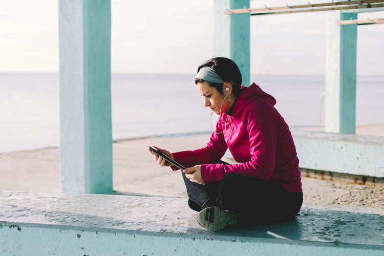 Woman using mobile phone while sitting by sea
