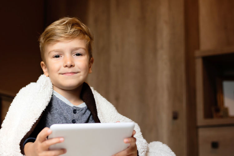 Portrait of boy holding mobile phone