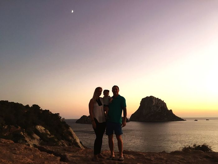 Family standing on cliff by sea against sky during sunset