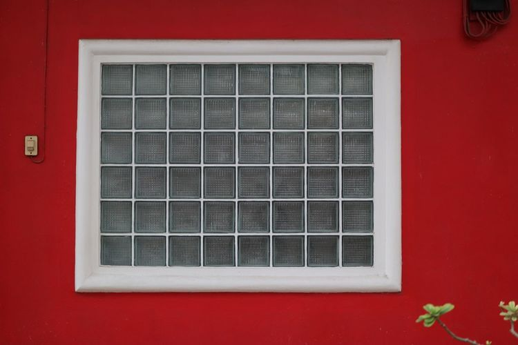 Close-up of window on red wall