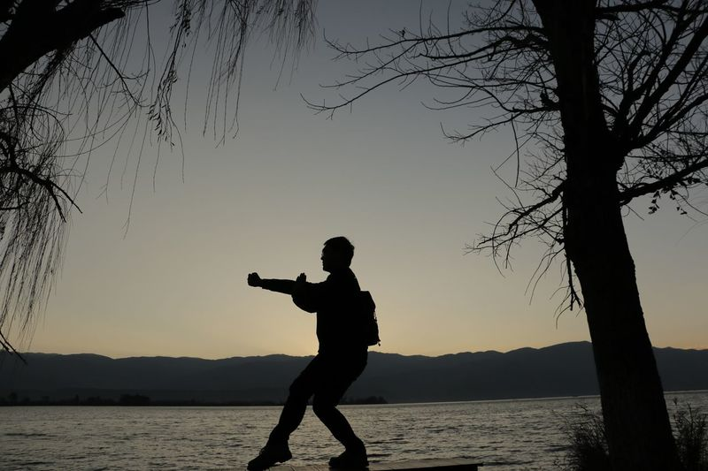 Sunrise Silhouette Beauty In Nature Real People Nature Lifestyles One Person Holding Sky Men Outdoors Tree Water Clear Sky Standing Leisure Activity Day The silhouette of me while waiting sunrise at Lake Qionghai in Xichang, China.