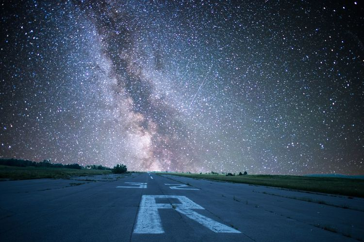Airport runway against star field sky at night