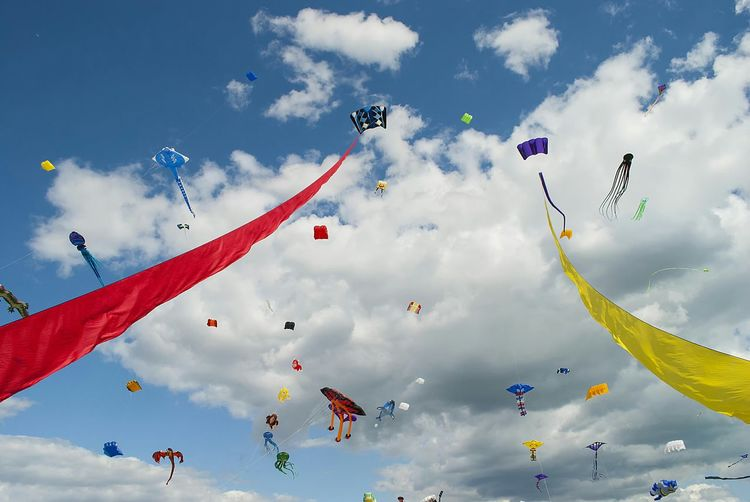 Low angle view of colorful kites flying against sky