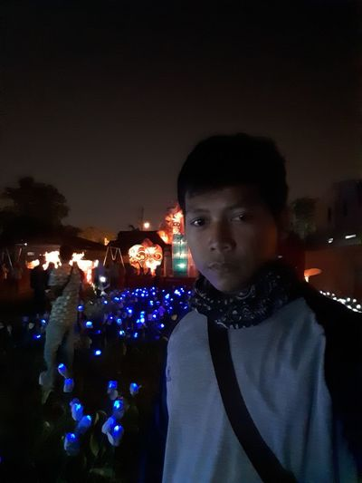 Portrait of young man standing against illuminated city at night