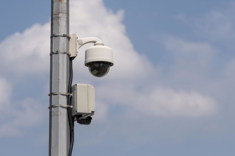 Low angle view of security camera against cloudy sky during sunny day